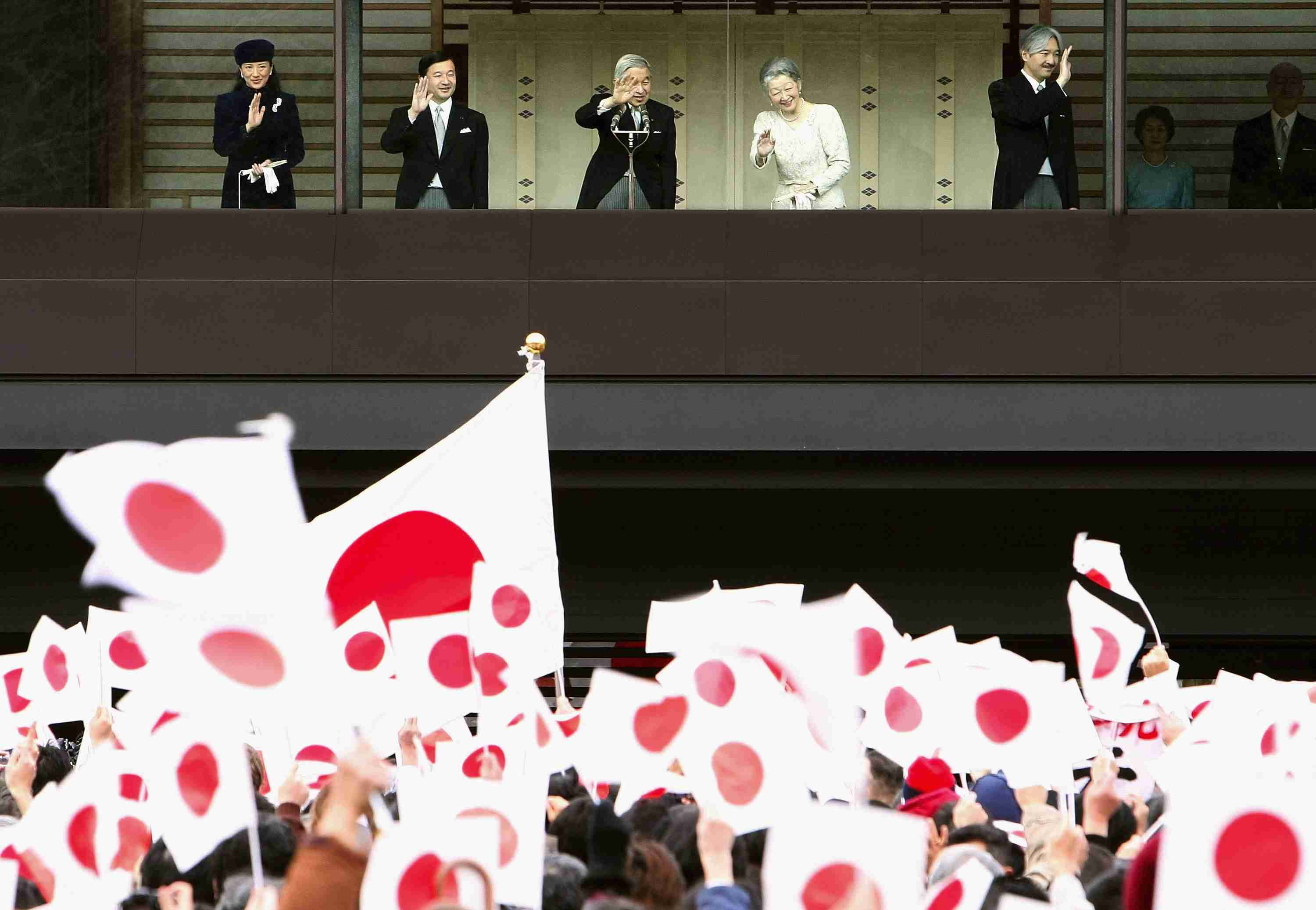 A crowd waving flags for the Emperor's Birthday Celebration in Japan