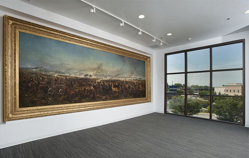 large painting of the battle of gettysburg on a gallery wall. There is a window on the wall perpendicular to the painting