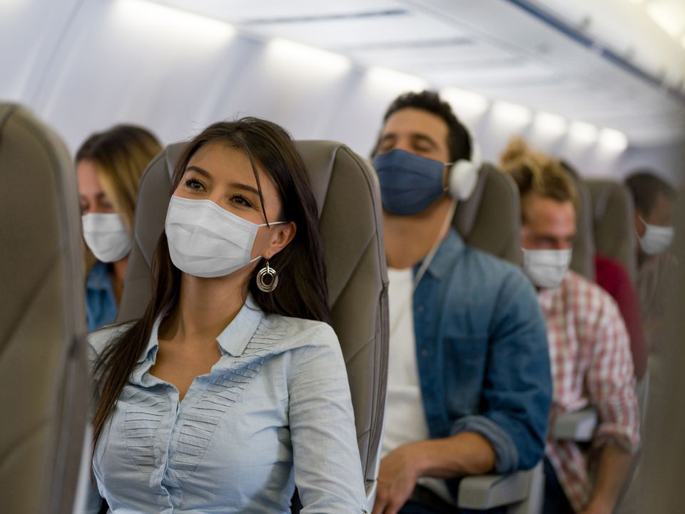 Portrait of a Latin American Woman traveling by plane wearing a facemask during the COVID-19 pandemic