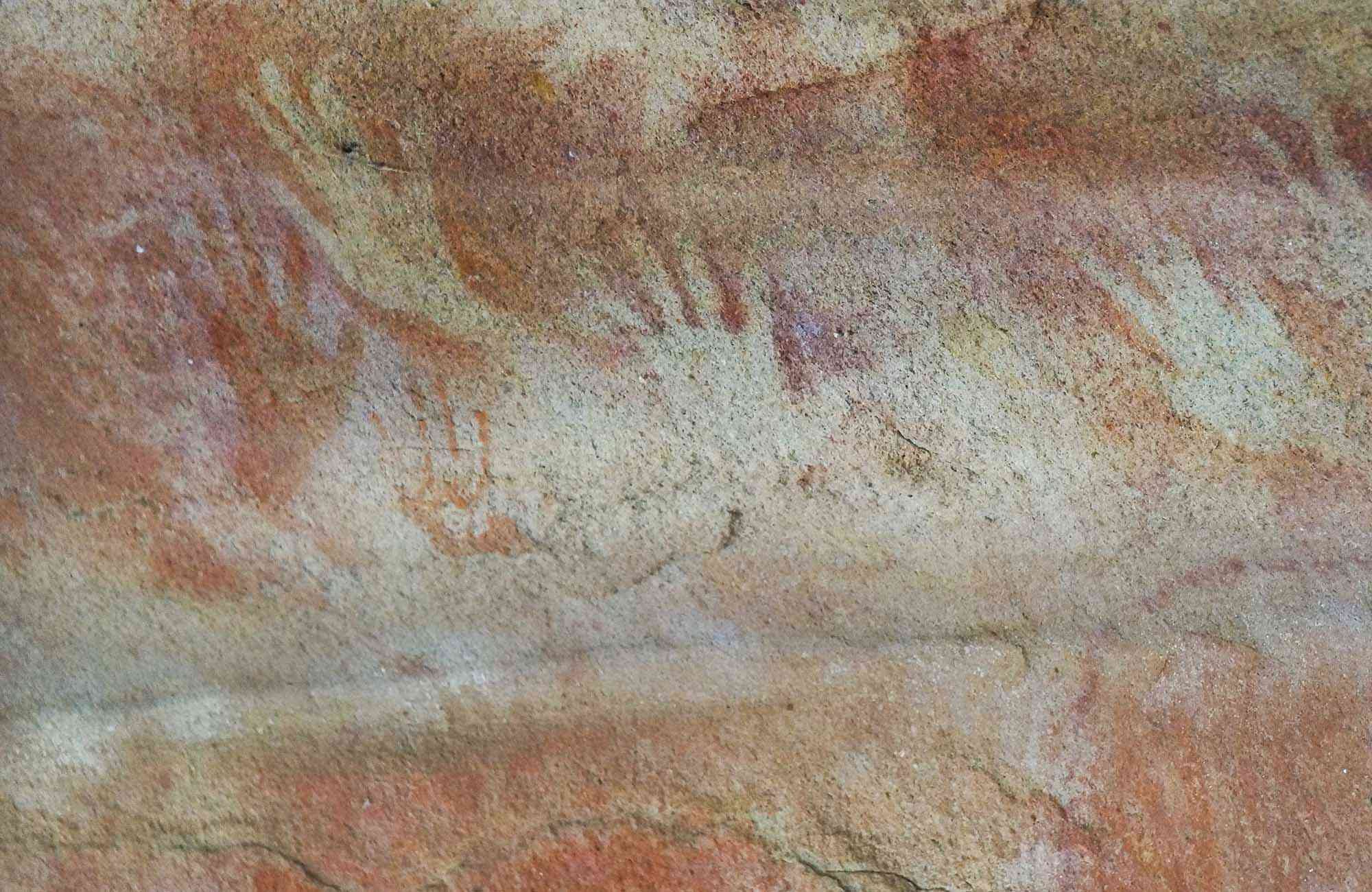 Reddish rock wall with hands printed on it
