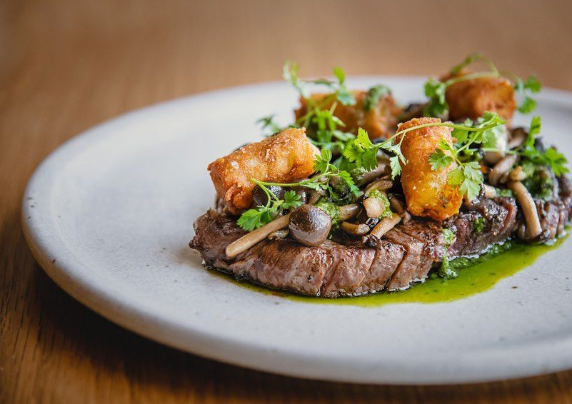 sliced steak on a plate topped with tater tots small mushrooms and fresh herbs