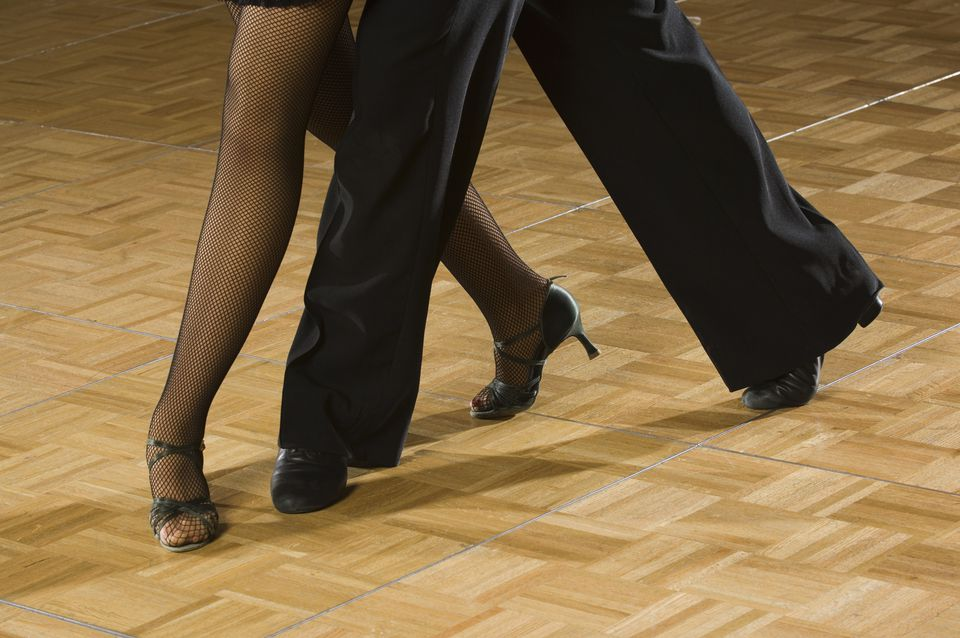 Close up of the legs of a couple salsa dancing.