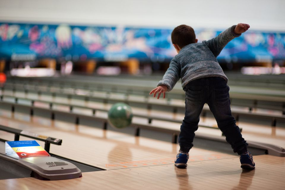 Boy playing ten pin bowling