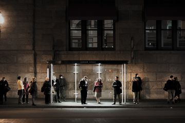 People waiting at bus stop outside of South Station in Boston Massachusetts