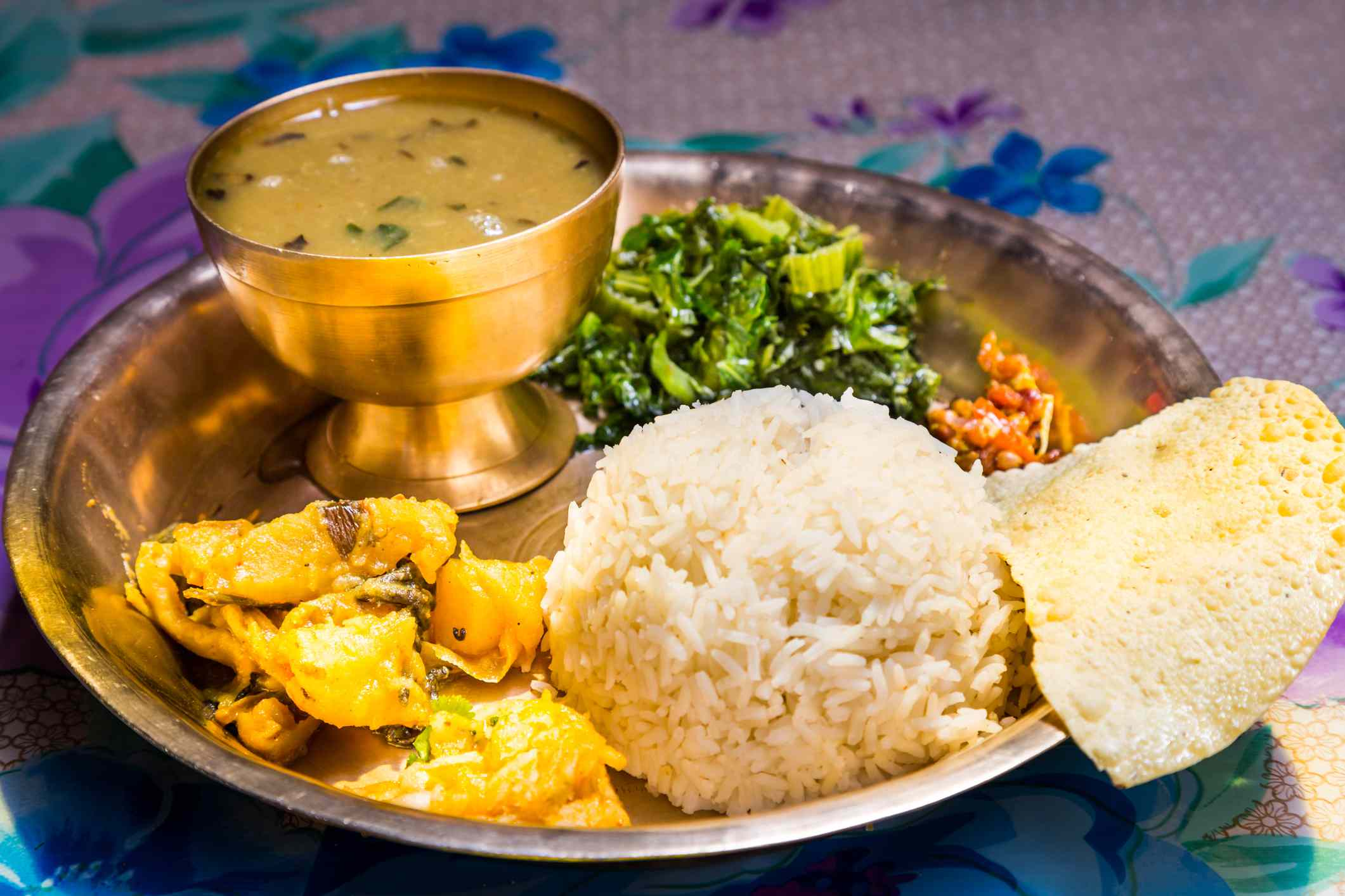 platter of food with potato curry, rice, papad, green vegetable and brass bowl of soup