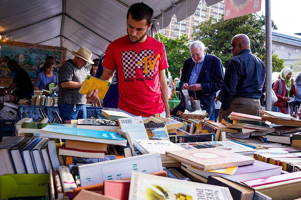 A young man wearing a MTV t-shirt exploring a large pile of books among other people exploring books at a tent at the Baltimore Book Festival, Baltimore, Maryland, September, 2013.