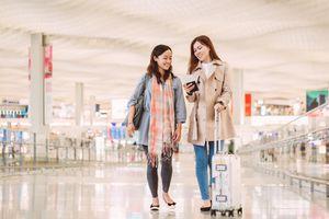 Women walking through airport looking at passport