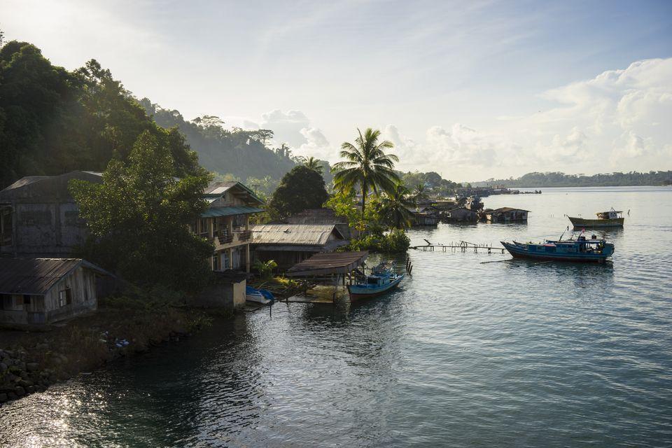 Barcos de pesca y destartaladas casas en la costa.