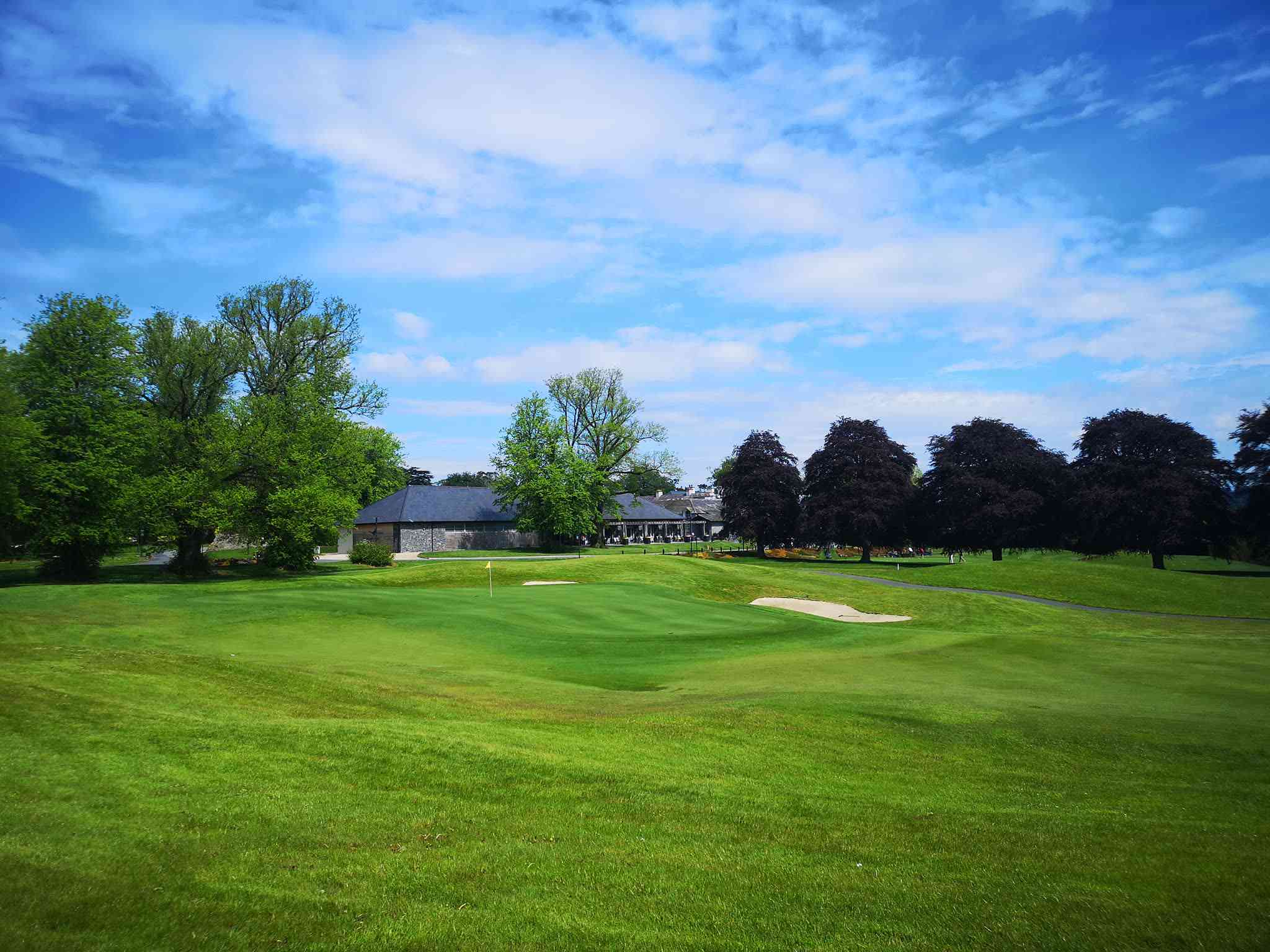 golf greens and blue sky with clubhouse in distance