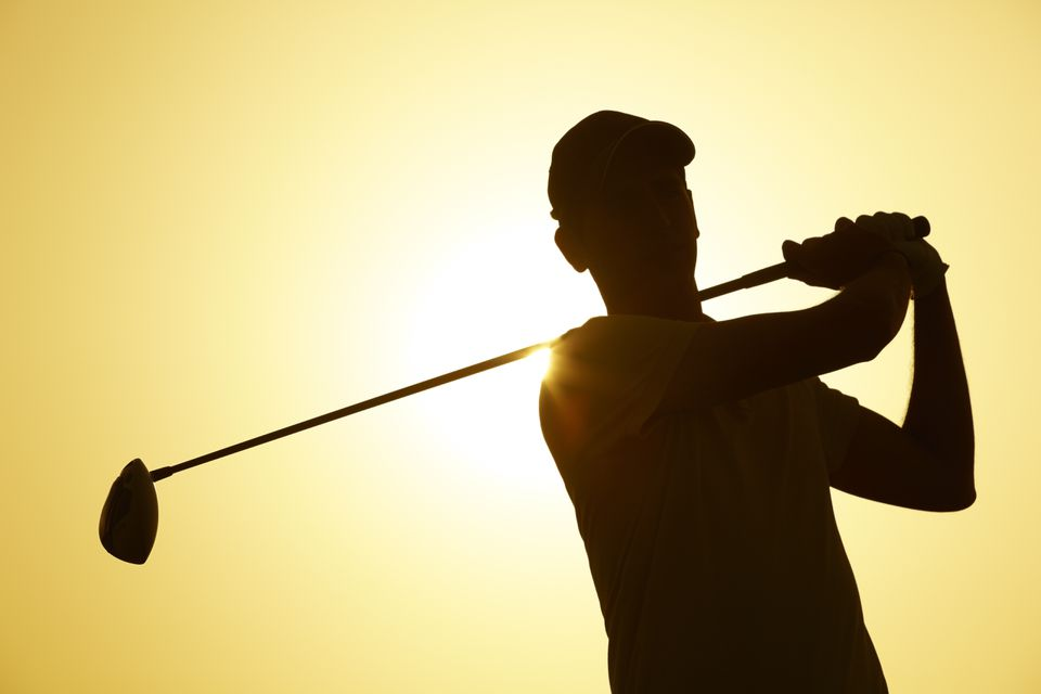 Silhouette of golfer against the sun
