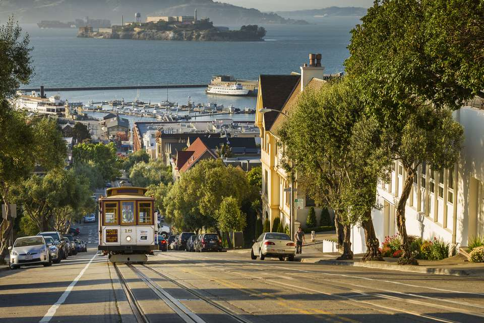 San Francisco city tram climbs up Hyde Street with Alcatraz beyond, San Francisco, California, United States of America, North America