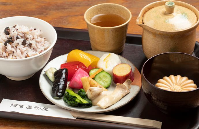 Plate of pickled vegtables with rice, green tea, and a dessert all on a tray with chopsticks