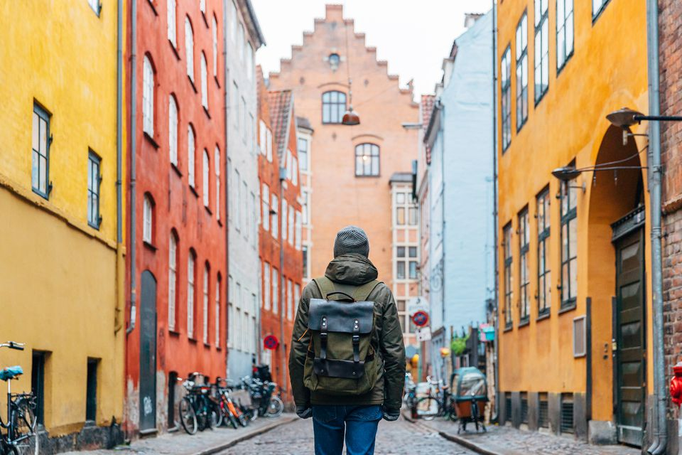 Young man with backpack walking in the streets of Copenhagen old town