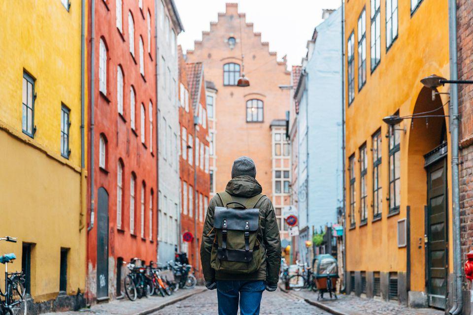 Hombre joven con mochila caminando por las calles del casco antiguo de Copenhague
