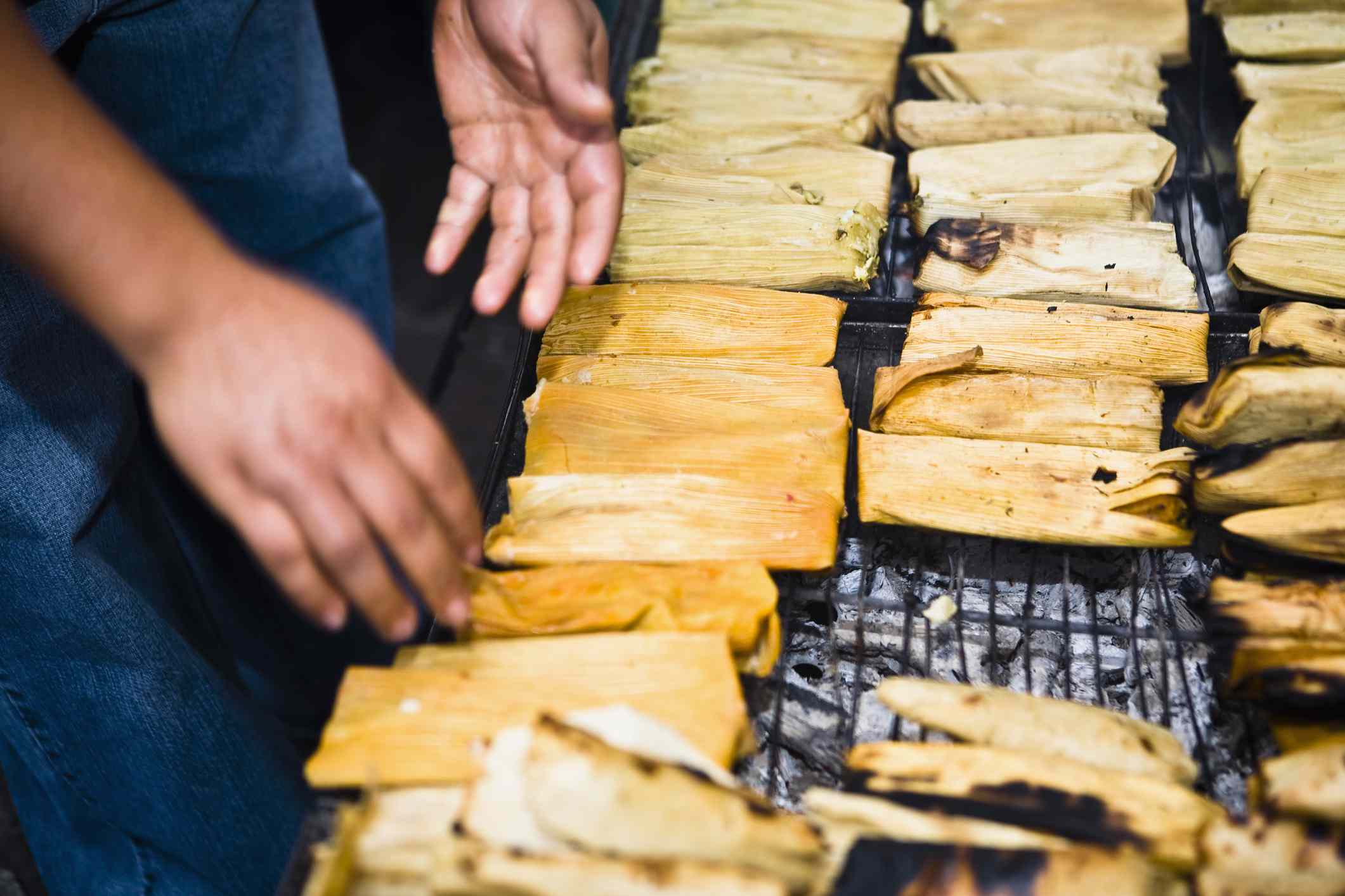 Mid section view of a man roasting tamales on barbecue grill, Zacatecas State, Mexico