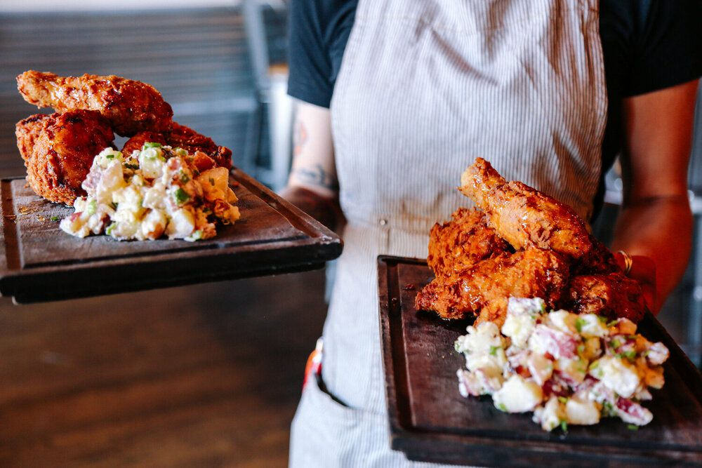 Torso of a waitress holding two wooden board with fried chicken and potato salad