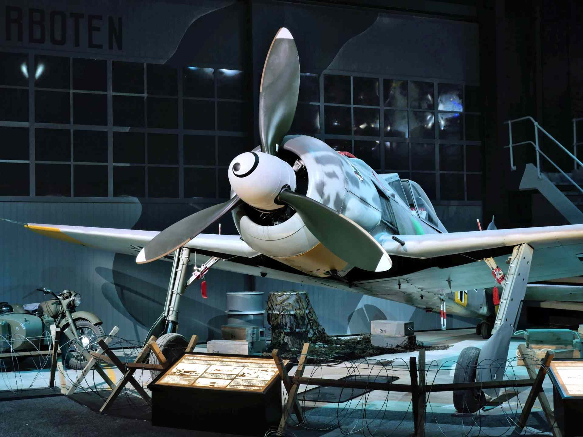 White propeller plane in a hangar-style aviation museum display