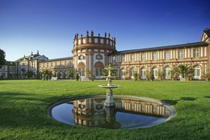 Large palatial building in Wiesbaden with a green lawn and small pond with a bird bath in the middle of it