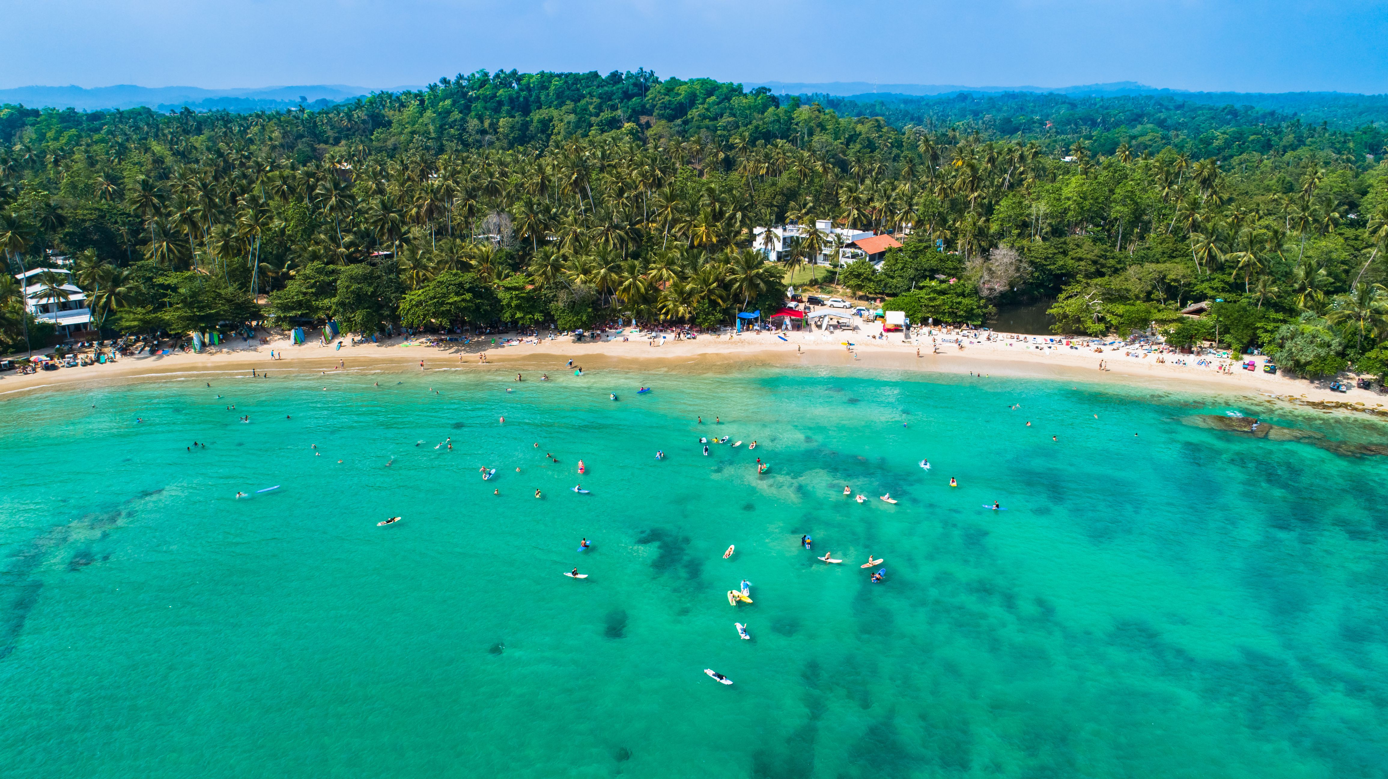 Aerial view of blue water and surfers at Dickwella Beach, Sri Lanka