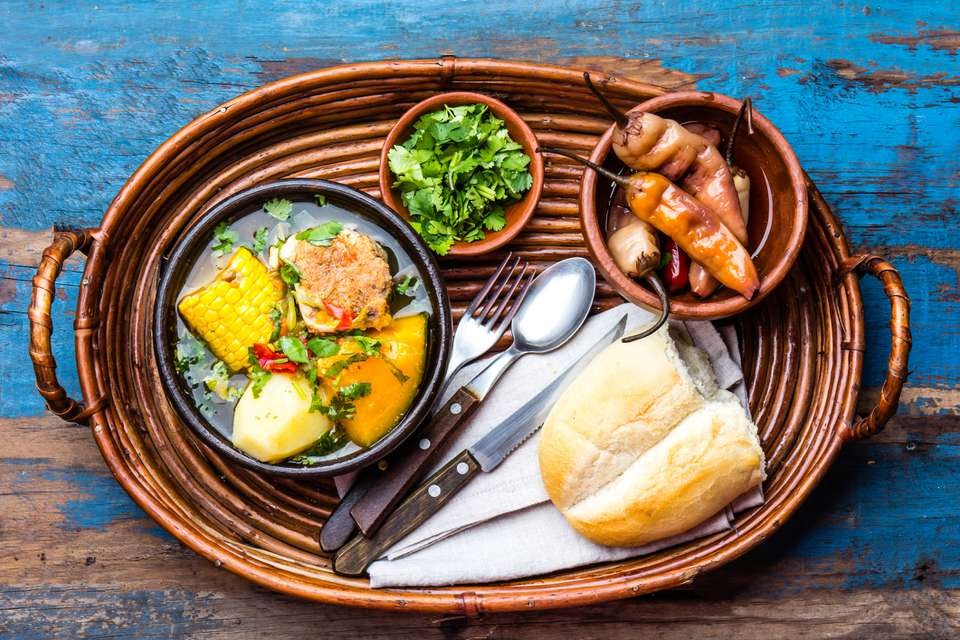 woven tray with bread, cilantro, pickled peppers, and a bowl of soup