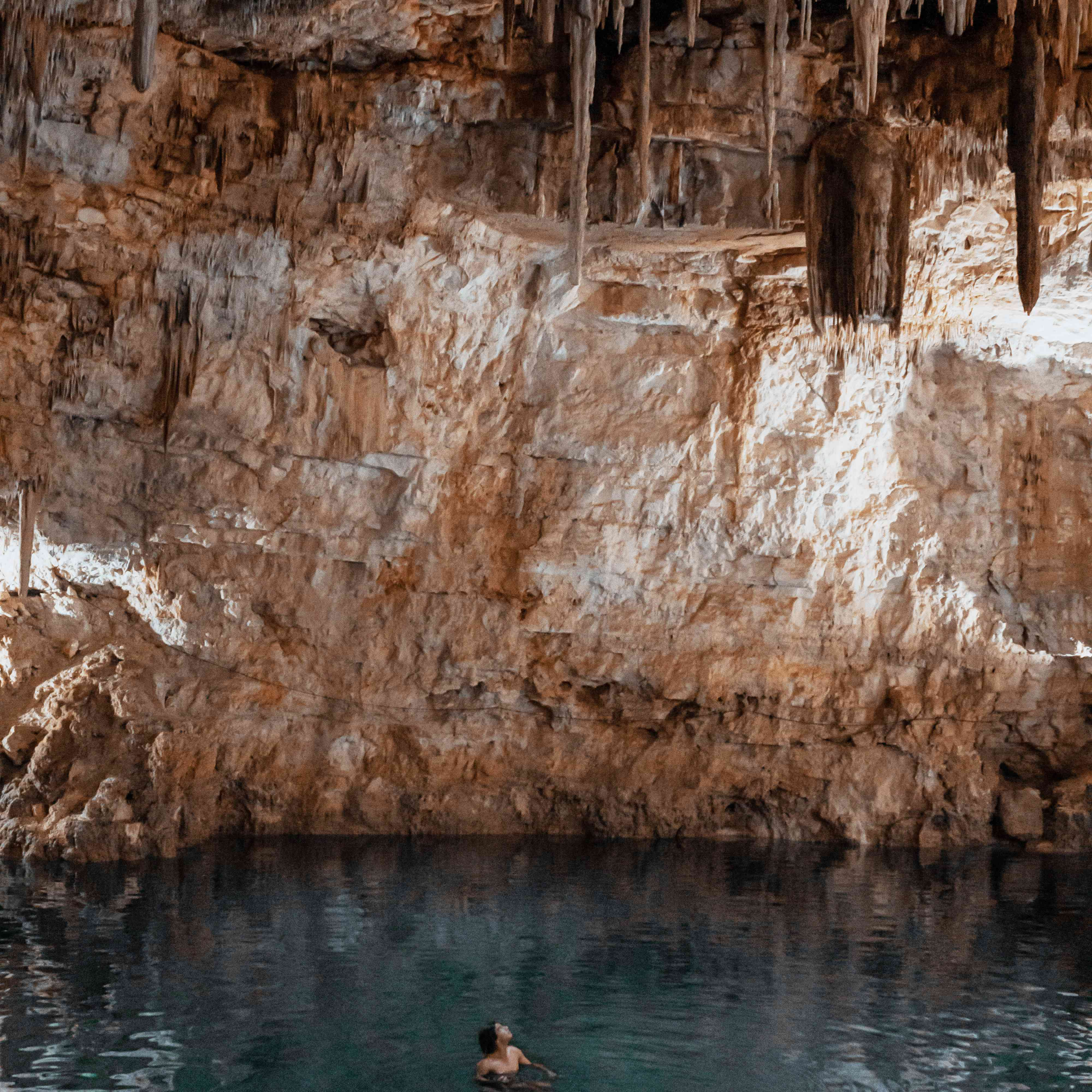 A man swimming in an underground cenote