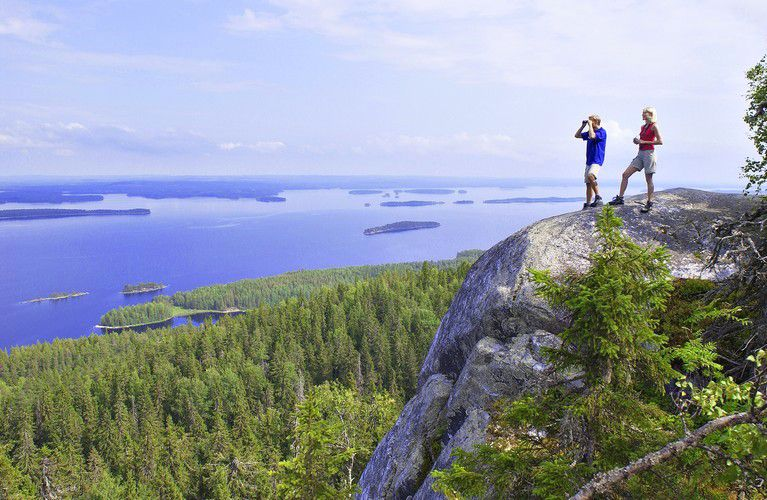 Two people hiking near a lake in Finland