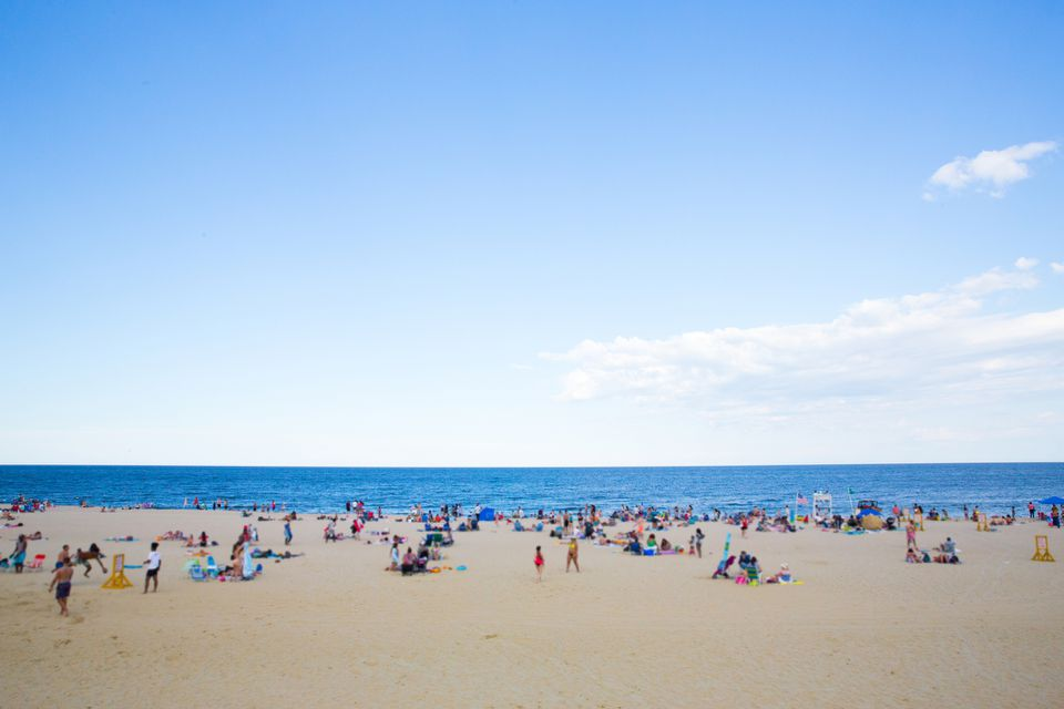 Crowded New England beach with sunbathers on sunny day