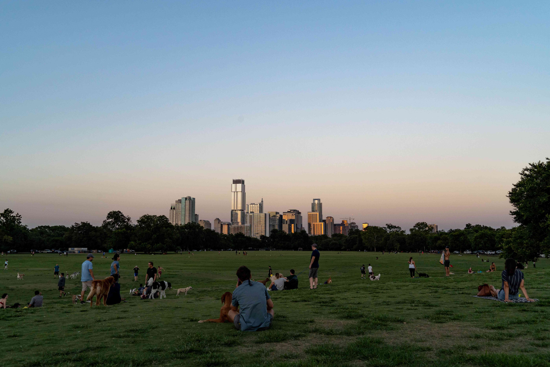Gente sentada en un gran campo de hierba en el Parque Zilker