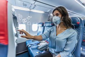 A woman flying on delta with a mask, touching the screen. White lines illustrated all around her