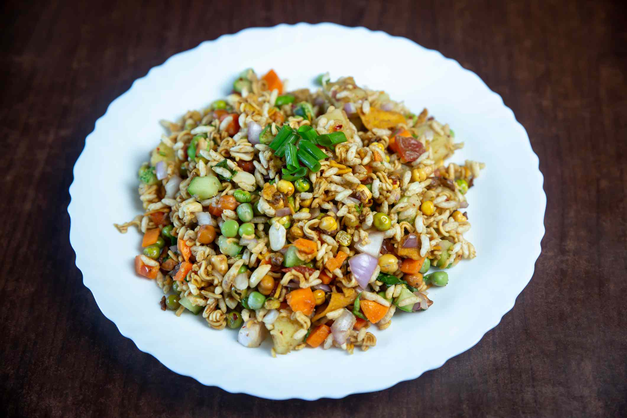 white plate on a table with a combination of chopped vegetables and pulses