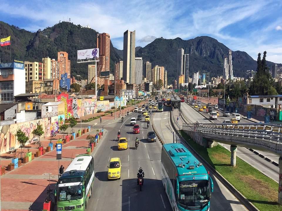 Vista de alto ángulo de automóviles en carretera en la ciudad con montañas en el fondo