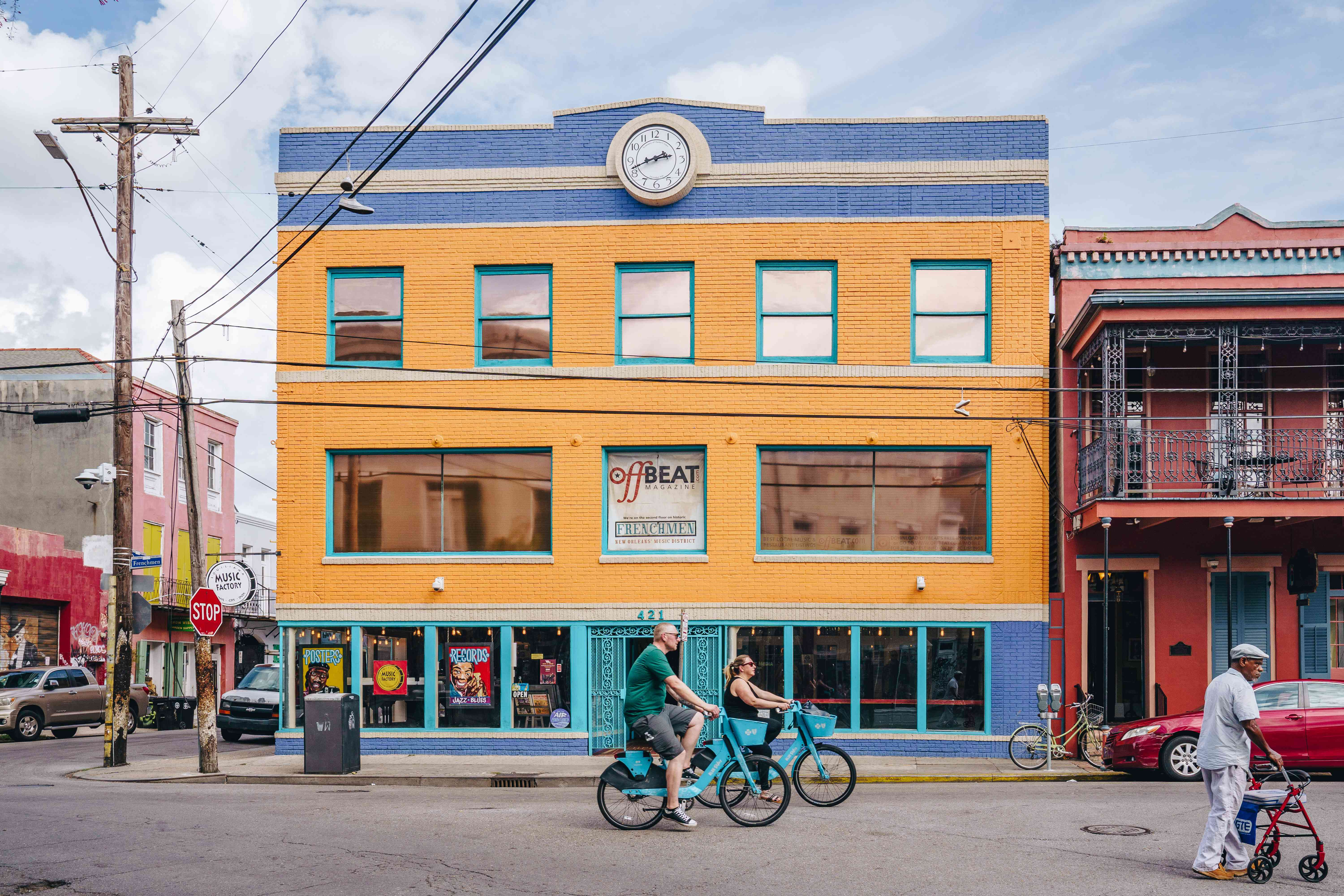 People biking by colorful buildings on Frenchmen street