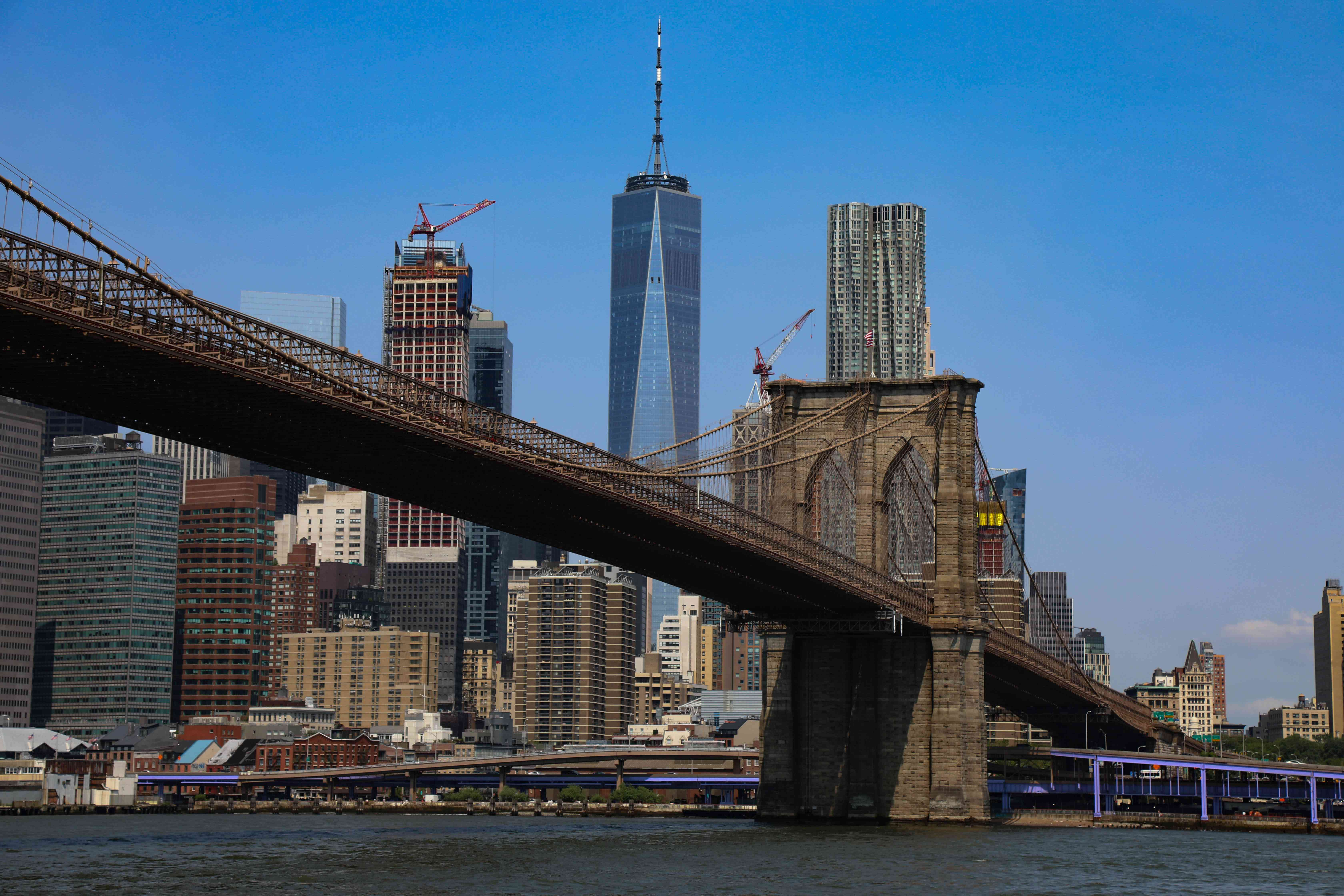 A view of the Brooklyn Bridge with the Manhattan skyline behind it.