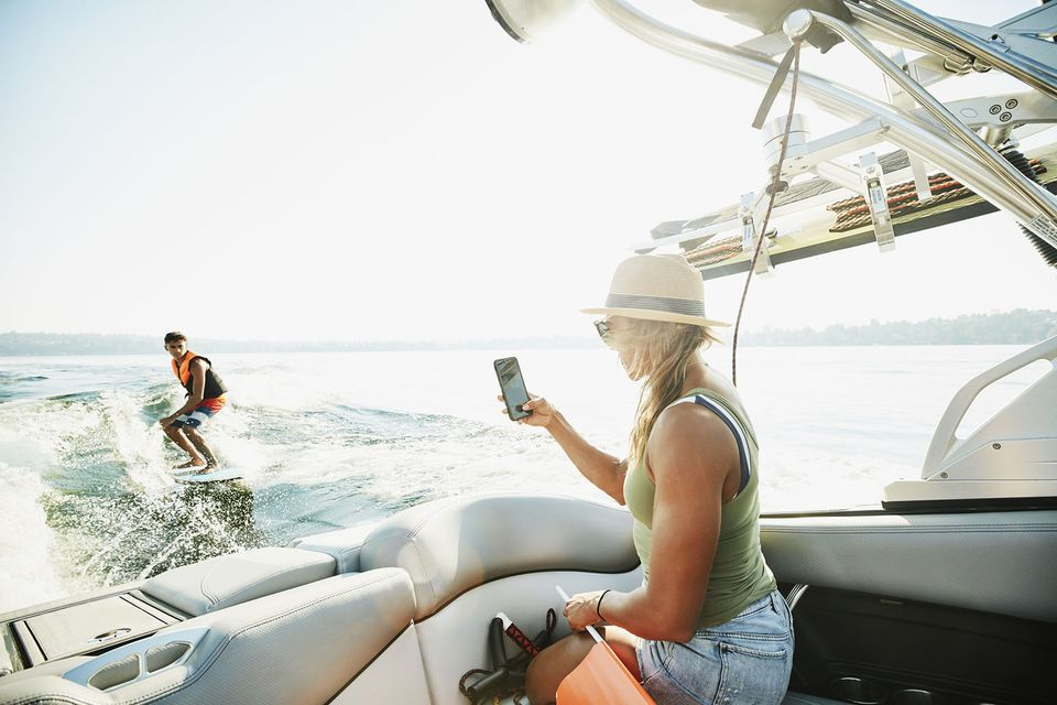 Mother taking photo with smart phone of teenage son wake surfing behind boat on summer afternoon