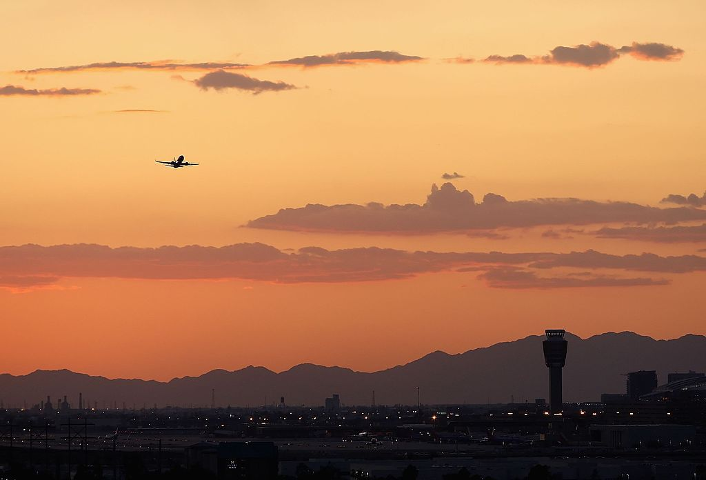 A plane takes off into the sunset above Sky Harbor Airport.