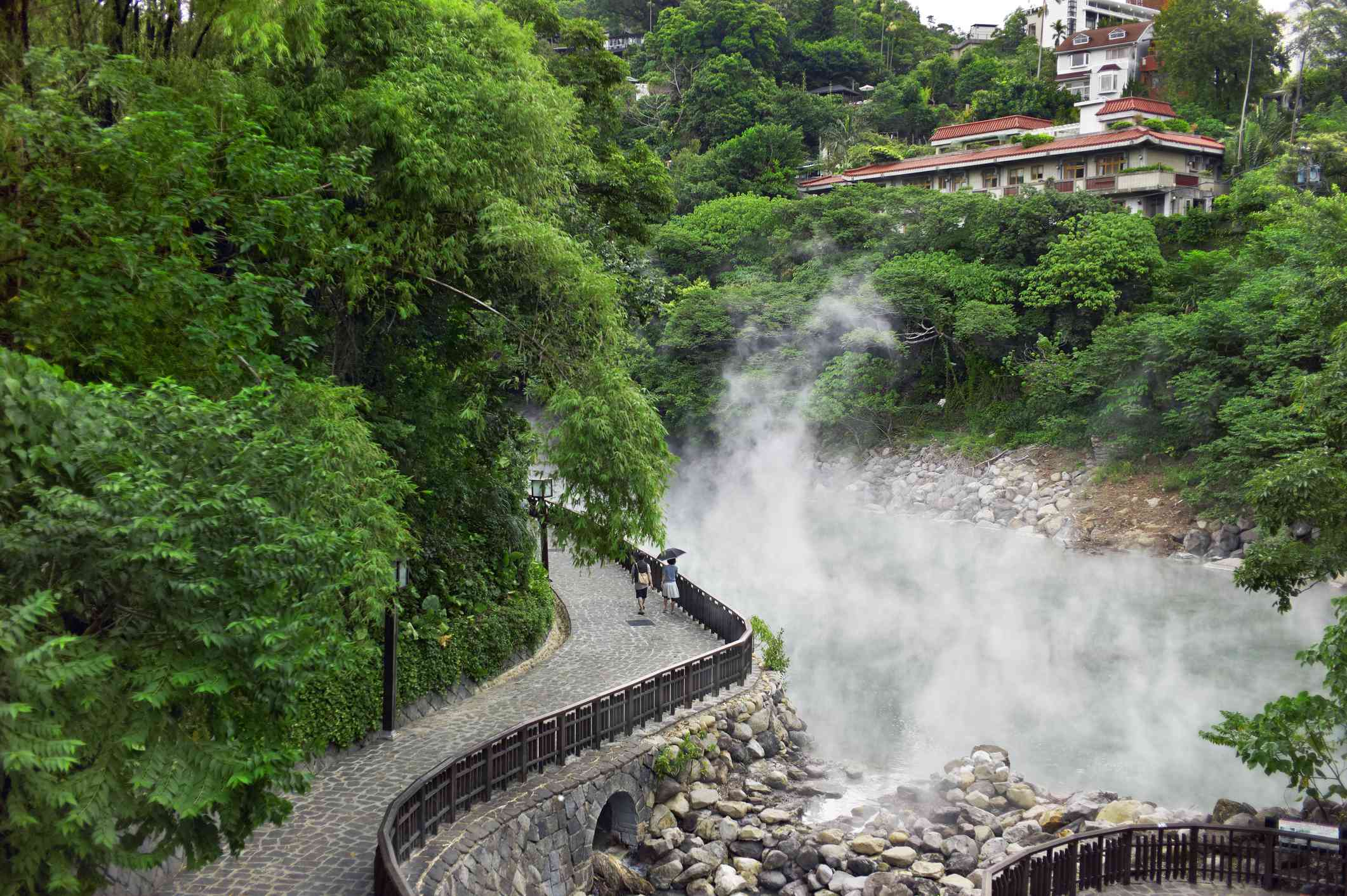 couple waking up a curving path next to a hot spring in Taipei's Beitou District