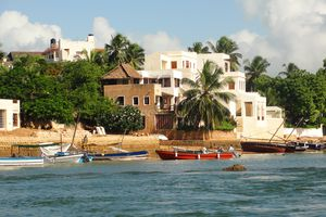 Dhows And Boats Moored At Shore Against Buildings