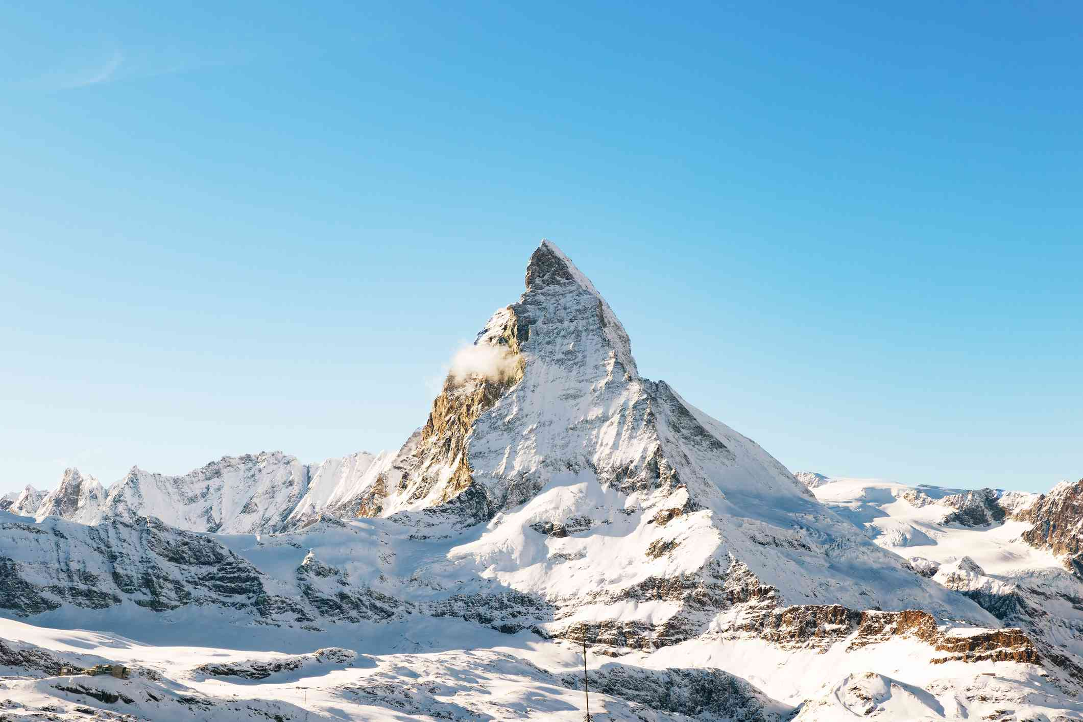 Panorama of the Matterhorn mountain range, covered with fresh snow, and blue sky in the cloudless background. Christmas season, winter and ski slopes on the Swiss Alps.