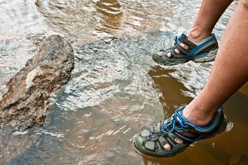 Someone wearing water shoes stepping into a lake