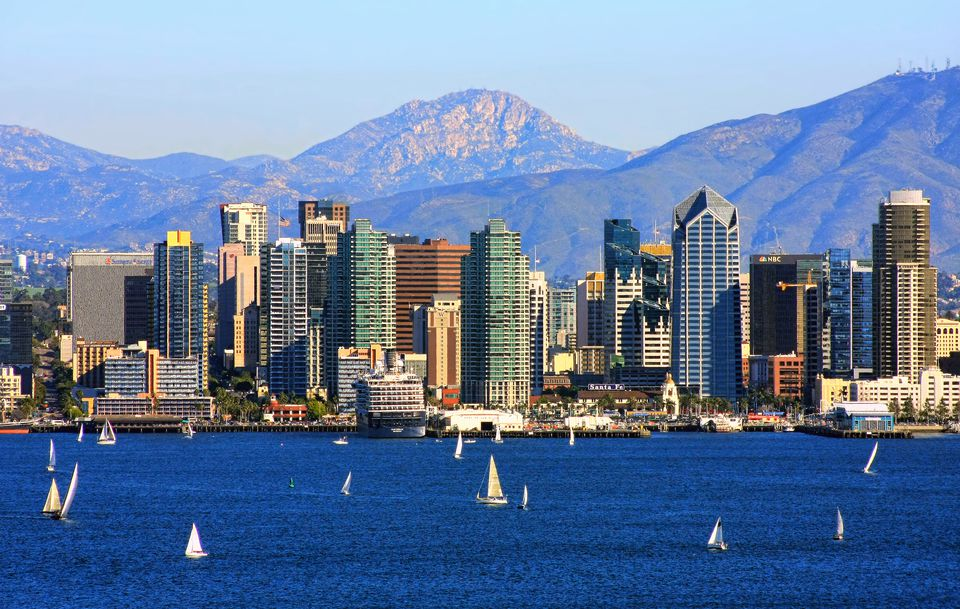 San Diego skyline of skyscrapers with mountains in the back and a body of water in the bottom third of the photos. There are sailboats of various sizes throughout the water
