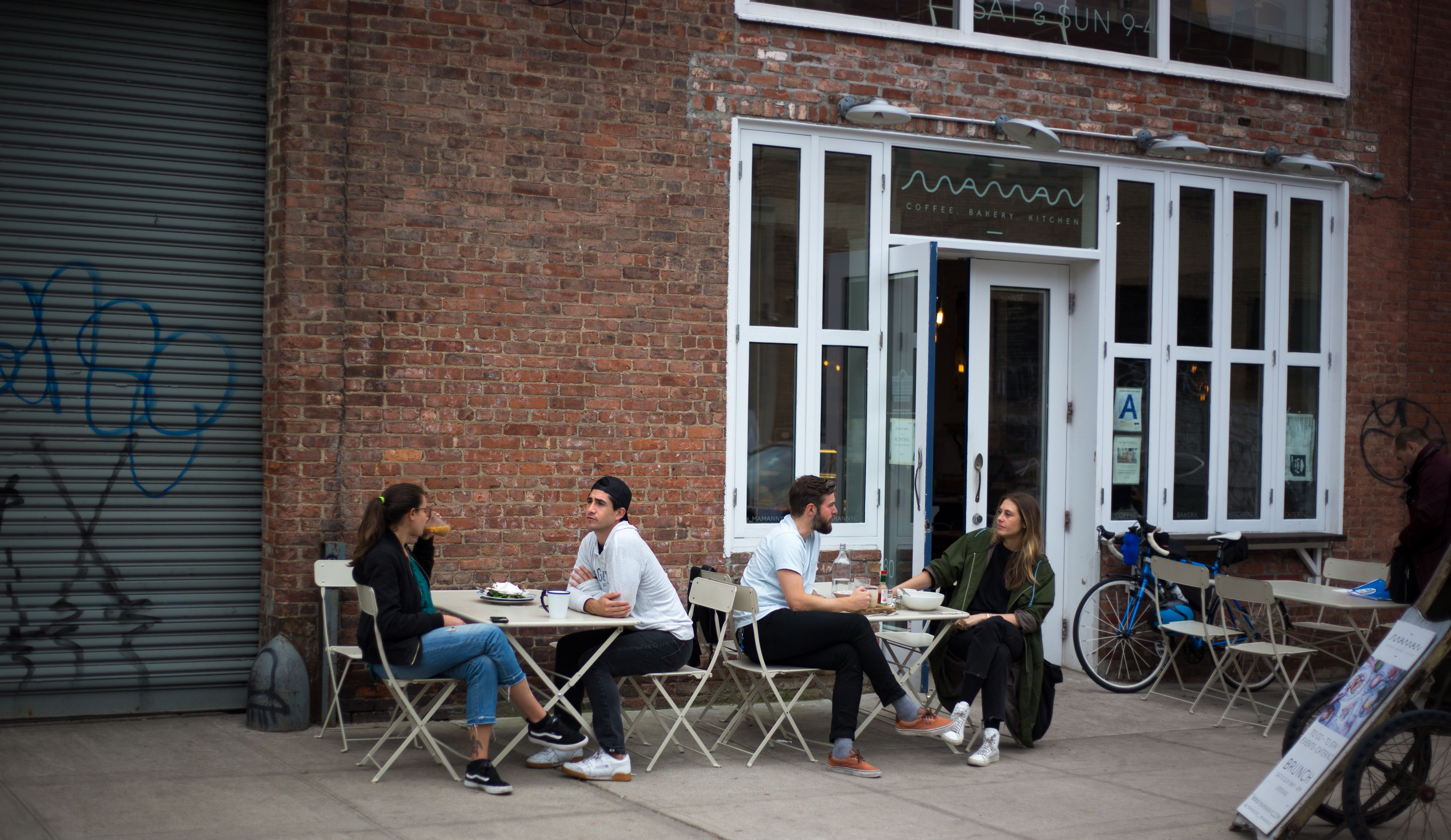 Millennials relajarse fuera del restaurante en Brooklyn, NY