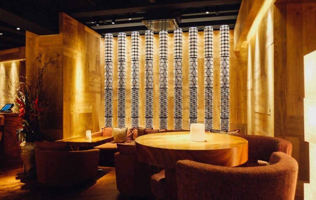 Zuma Bar in Rome with black and white lit pillars behind low tables