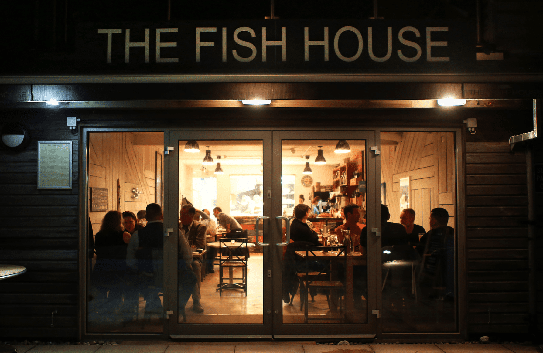 View of people eating inside The Fish House restaurant at night