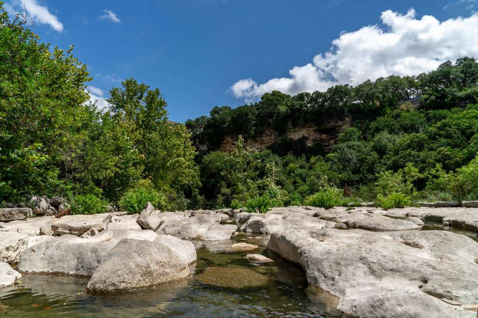 A creek surrounded by rocks and hilltops covered in green trees