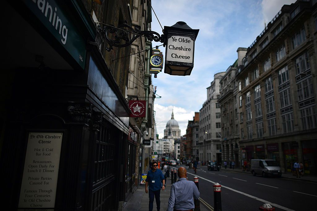 People walk past Ye Olde Cheshire Cheese, formerly a famous haunt for journalists, in Fleet Street in London.