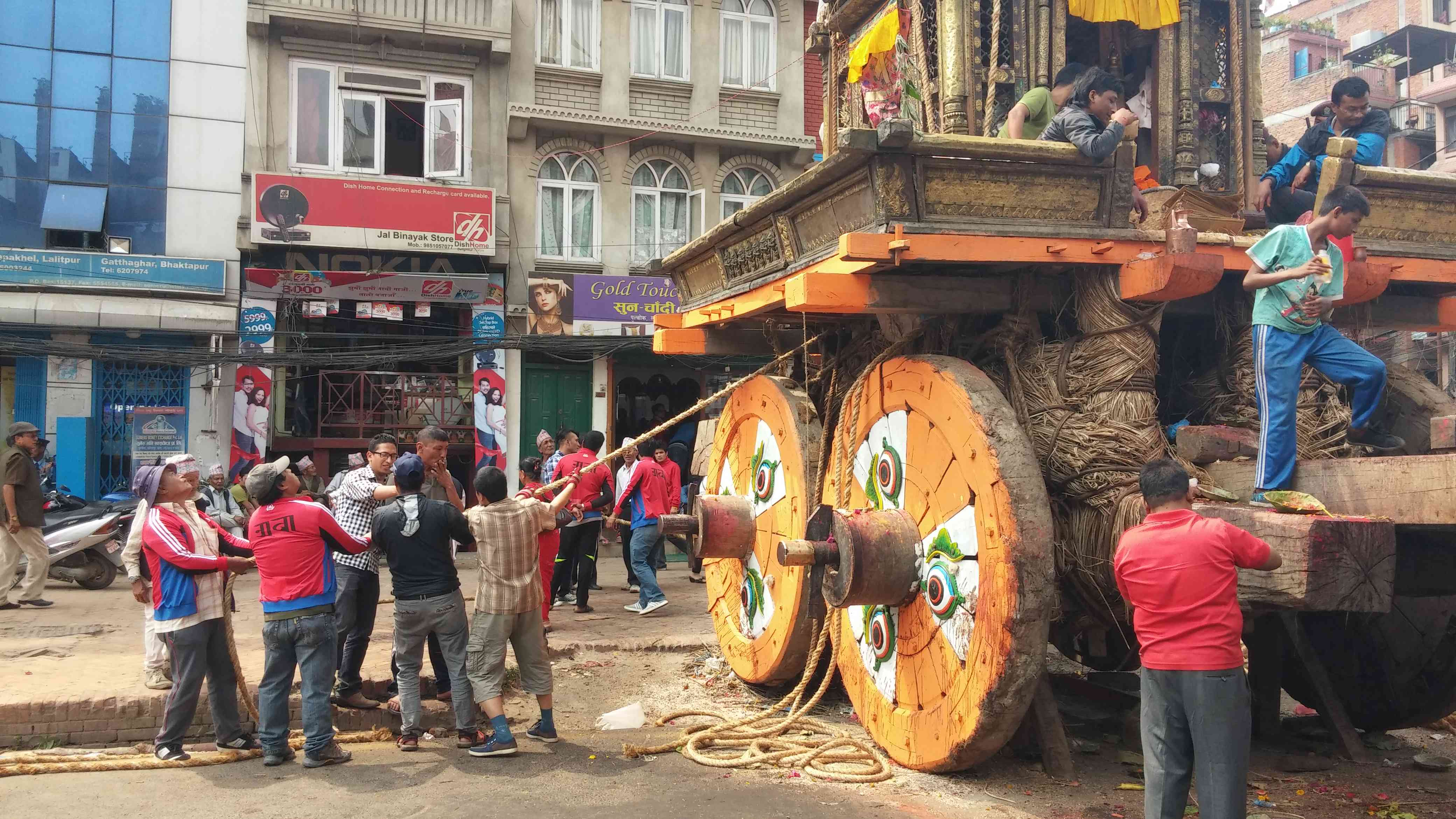 men pulling a rope attached to a large chariot with orange wooden wheels