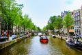 A small boat cruising down a canal in Amsterdam
