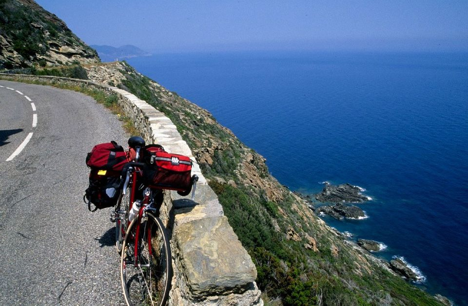 A bike parked along a scenic route in Italy that overlooks the sea