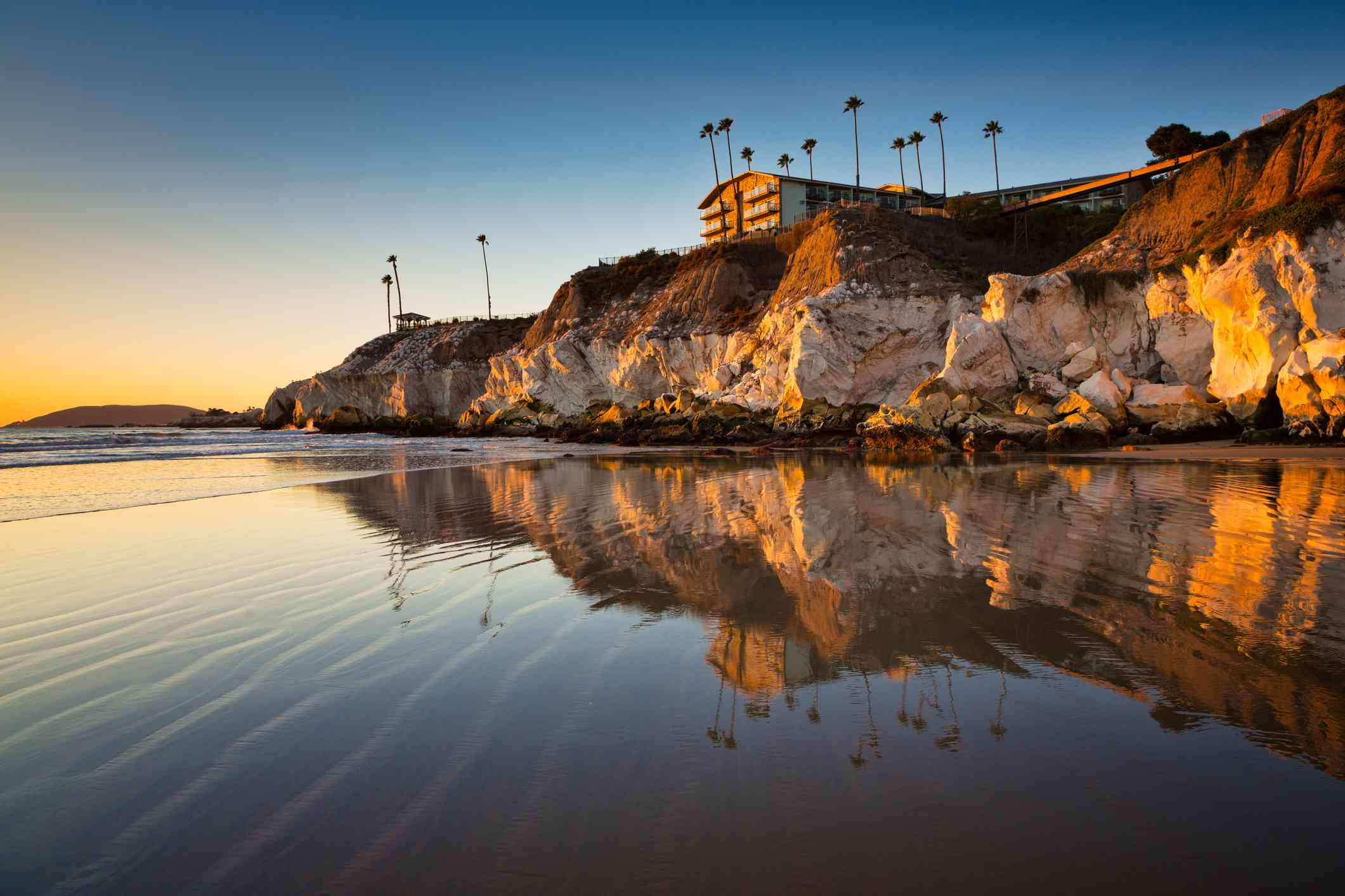 This is a photo taken near sunset at the north end of Pismo Beach, California. It was taken during low tide and the cliffs are reflected in the wet sand.