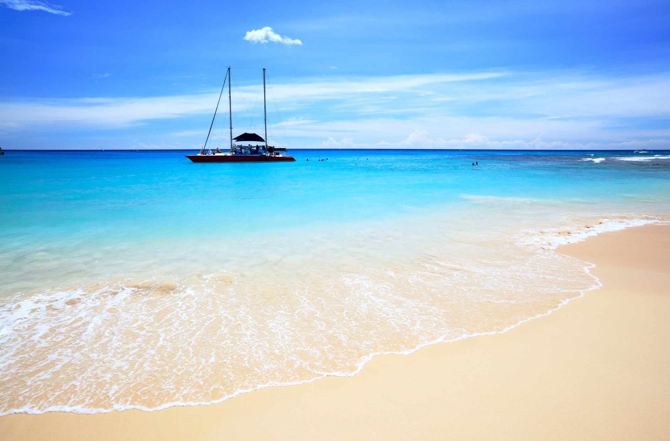 Boat on bright blue waters at Paynes Bay Beach